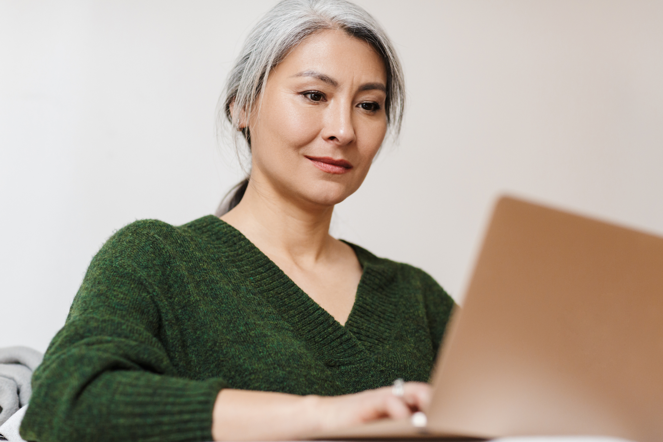329803286-mature-asian-woman-working-at-laptop-2160px