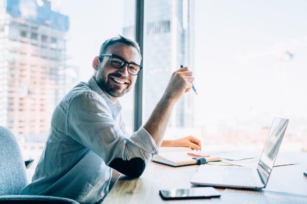MED-friendly-man-sitting-at-office-desk-600px